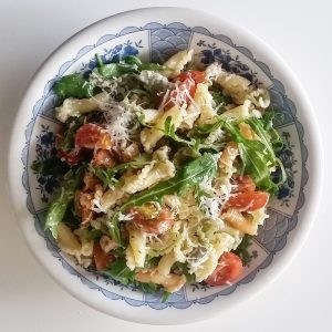 Cured manchego cheese and pasta salad with tomato and rocket